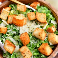 overhead image: wooden bowl of green salad with homemade croutons