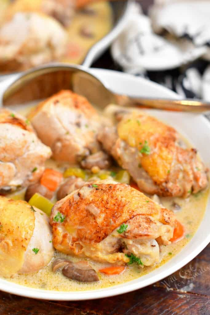 cooked meal of chicken thighs and legs with mixed vegetables in creamy white sauce