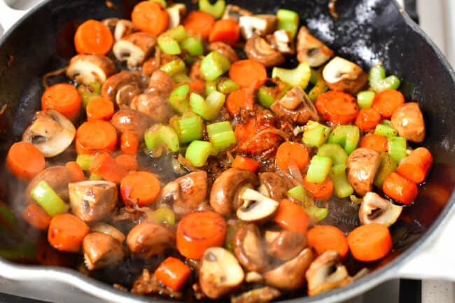 mushrooms, celery, carrot, and shallot cooking in pan of melted butter