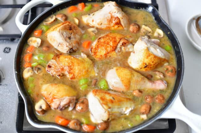chicken fricassee simmering in white skillet on stove top