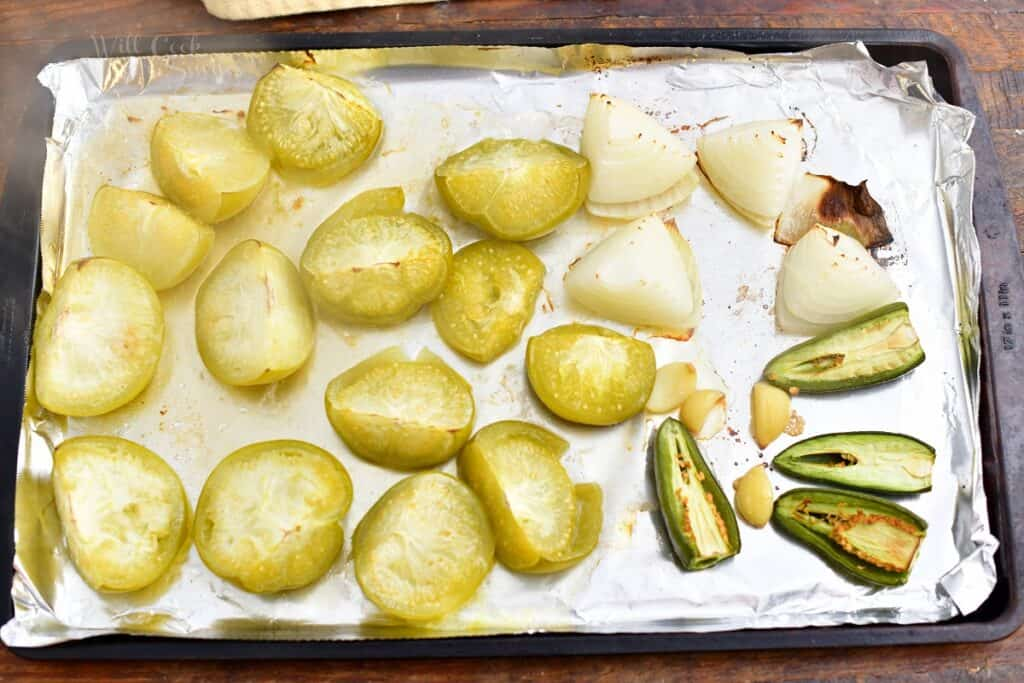 foil lined baking sheet with roasted onions, jalapenos, and tomatillos