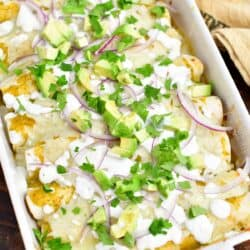 overhead: pan of green chicken enchiladas on a wooden surface with a towel