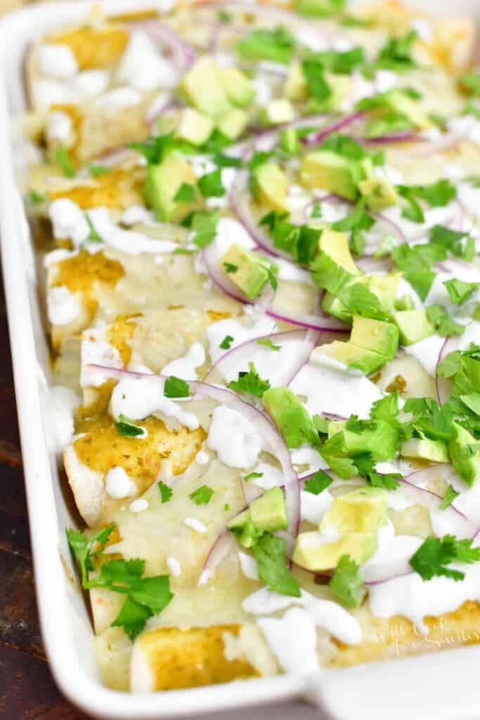 white pan of enchiladas verdes with garnish