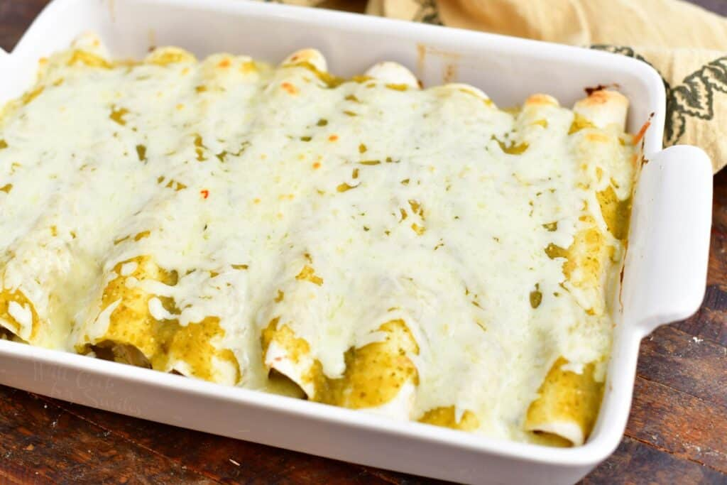 baked chicken enchiladas covered in green sauce and melted cheese in a white casserole dish