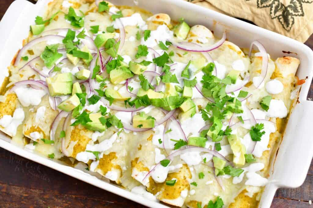 cooked pan of enchiladas verdes topped with red onion, avocado, and cilantro