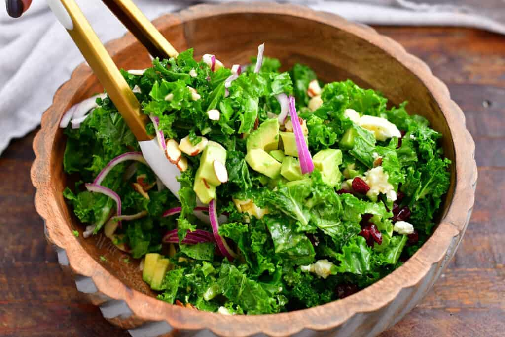 using wooden tongs to toss fresh kale salad before serving