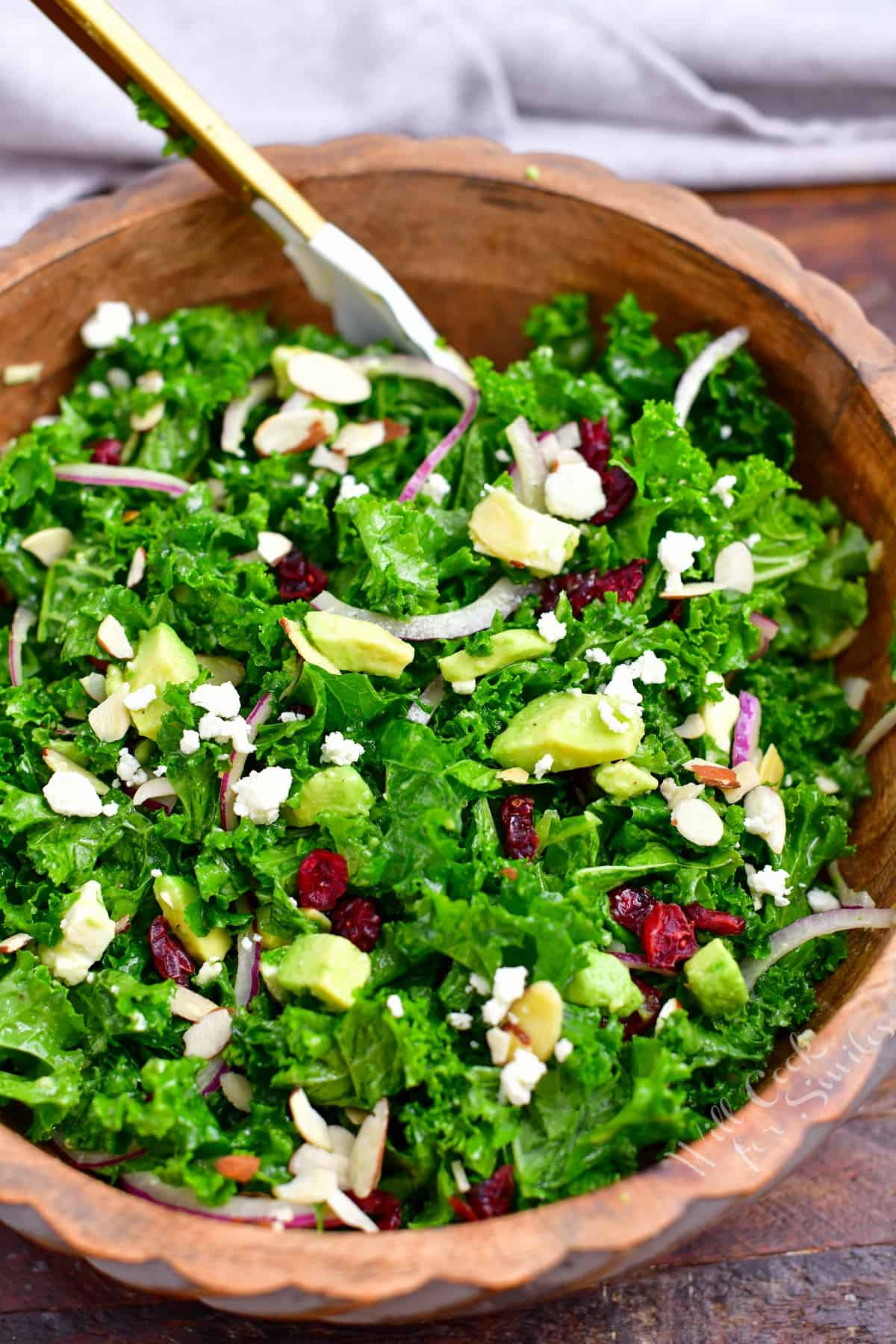 kale salad with almonds, avocado, dried cranberries, and feta cheese in wooden bowl