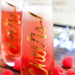 fresh raspberries scattered around two Kir Royale cocktails
