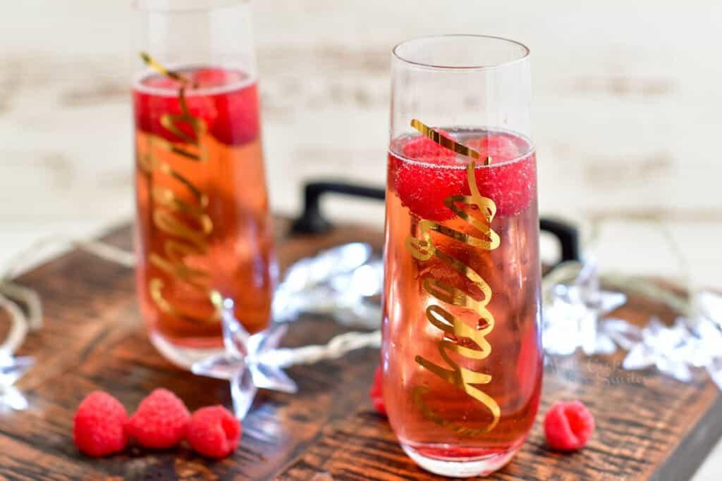 fresh raspberries floating in a Kir Royale cocktail