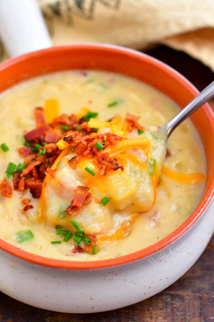 creamy soup topped with bacon, shredded cheese and chives in a white and orange bowl with a spoon