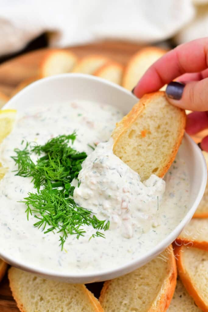 woman's hand dipping toasted baguette into bowl of creamy salmon dill dip