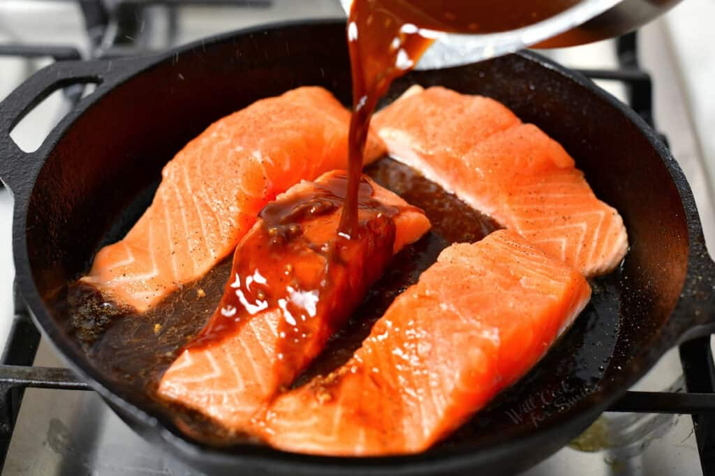 teriyaki sauce being poured over salmon fillets in a cast iron skillet