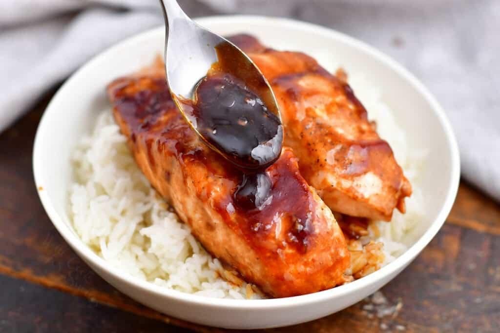 spooning sauce onto teriyaki salmon in white dish on bed of jasmine rice