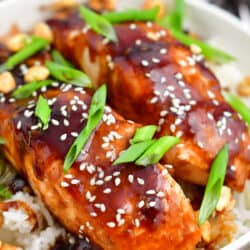 closeup: teriyaki baked salmon topped with scallions and sesame seeds on a bed of fluffy rice
