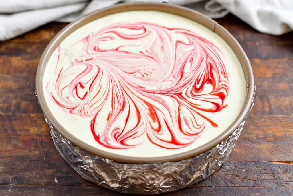 white chocolate cheesecake filling swirled with raspberry sauce in a springform pan with foil around the outside