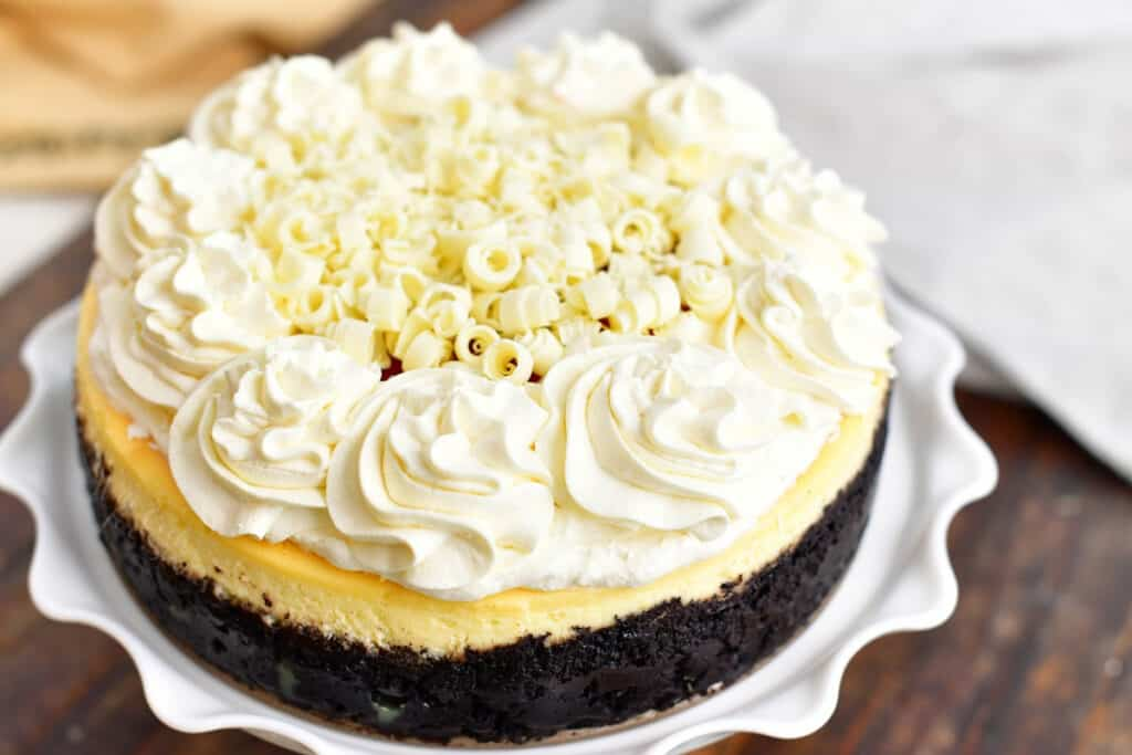 closeup: whole decorated cheesecake on a white cake stand