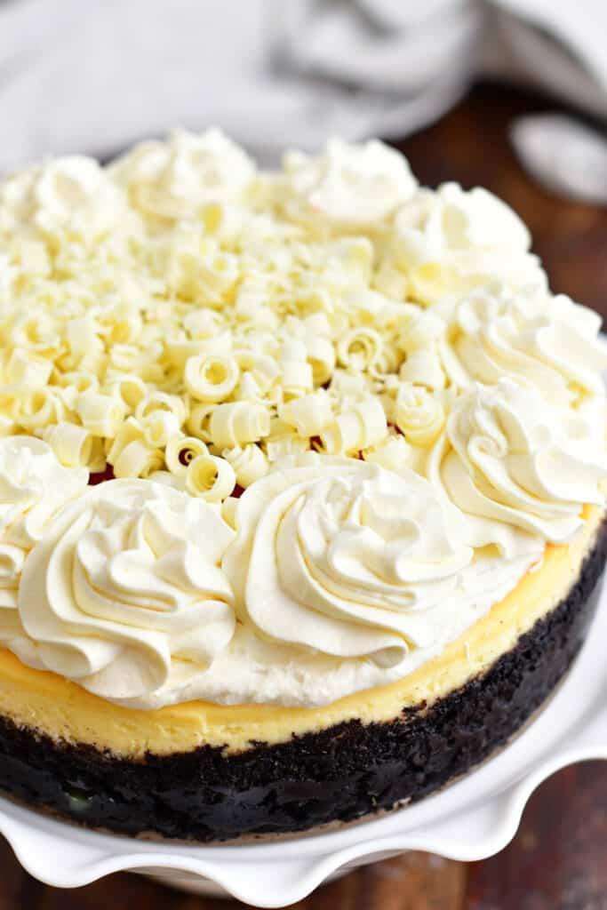 whole cheesecake with Oreo crust topped with frosting and white chocolate shavings