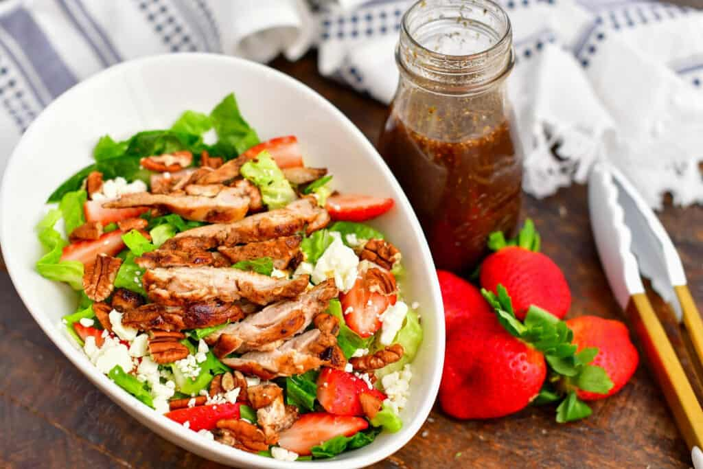bowl of salad with sliced chicken surrounded by patterned towels, jar of dressing, strawberries, and a pair of tongs