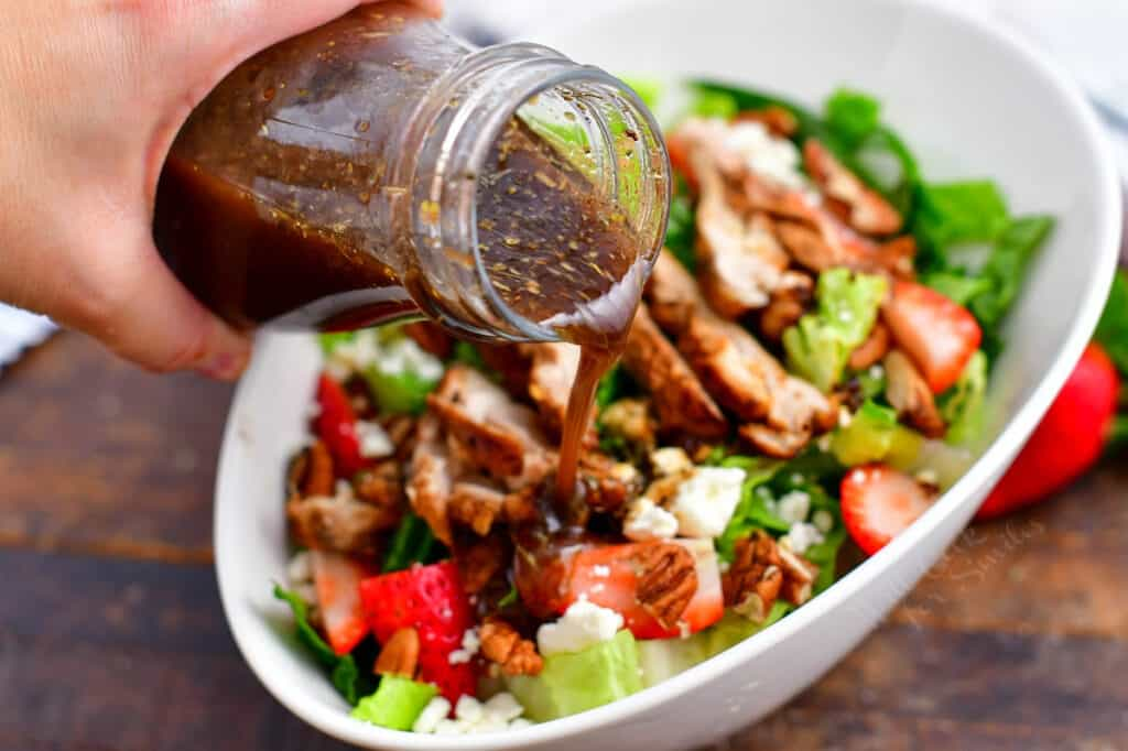 jar of balsamic vinaigrette being poured over a green salad with chicken