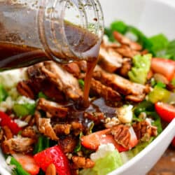 balsamic dressing being poured over a salad topped with chicken