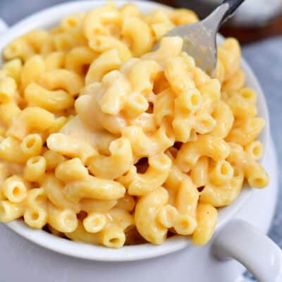 fork lifting creamy mac and cheese out of a soup bowl with handles