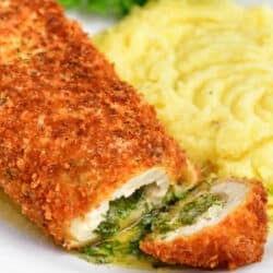 chicken kiev on plate with whipped potatoes. chicken cut open to reveal herb butter inside