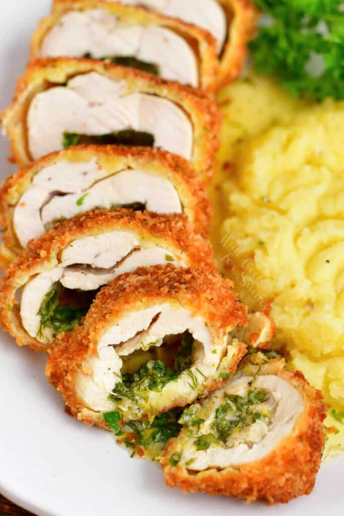 stuffed chicken breast cut into thin slices revealing herb butter inside