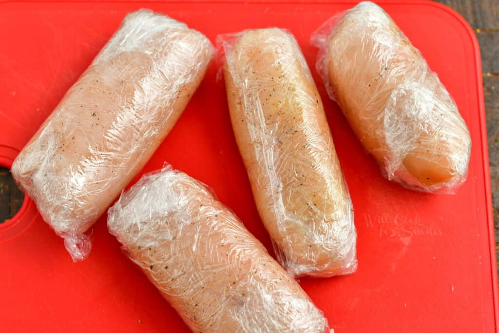chicken cutlets rolled into cylinder shape, wrapped in plastic wrap