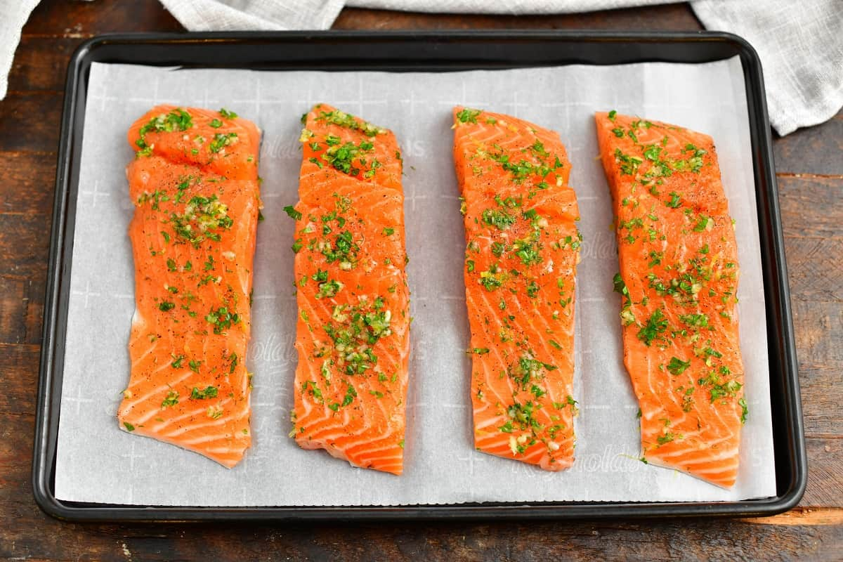 four pieces of raw fish on parchment lined baking sheet