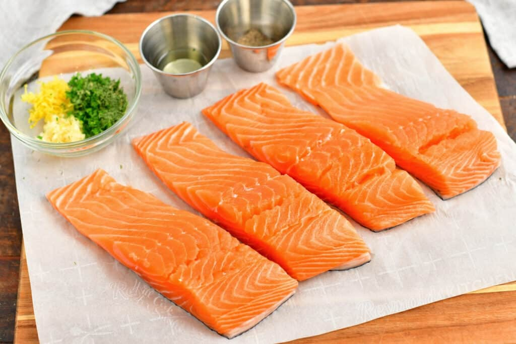 4 fresh salmon fillets on parchment paper with fresh herbs for healthy salmon recipe