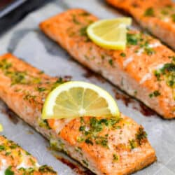 closeup image of oven baked fish topped with fresh herbs and lemon slices