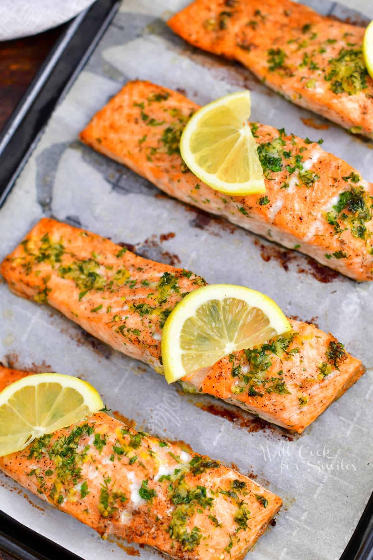 healthy baked salmon on baking sheet topped with slices of lemon