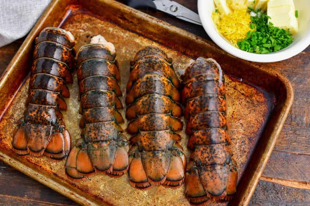 4 lobster tails on metal baking sheet