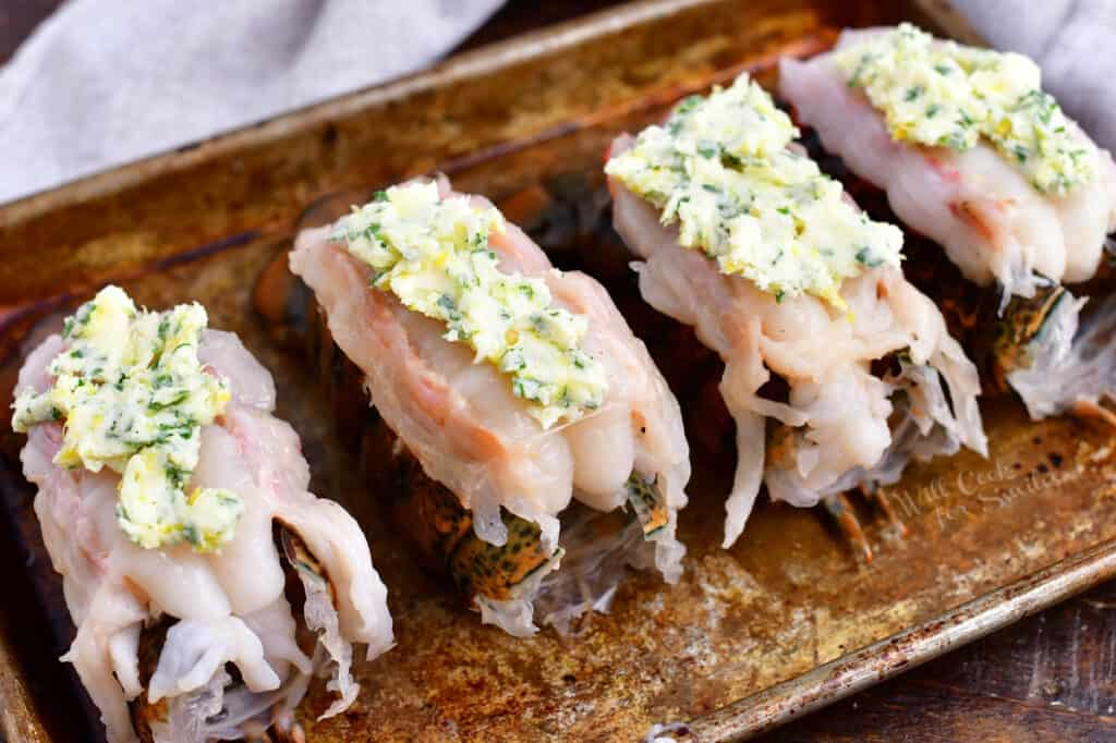 4 raw lobster tails topped with compound butter, ready for baking