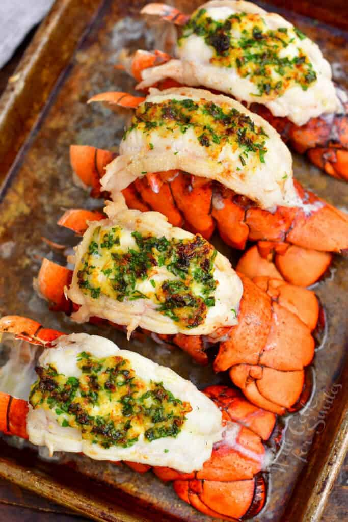 freshly baked lobster meat covered with herb butter sit on a sheet pan