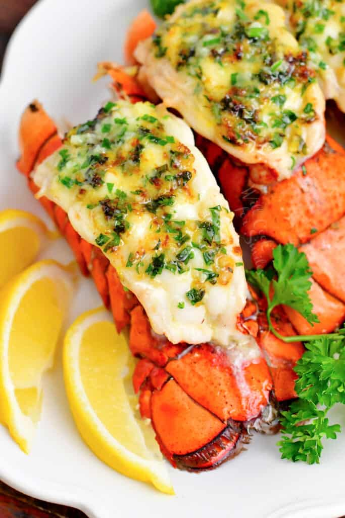 overhead image of a lobster tail on white plate with lemon slices and fresh parsley