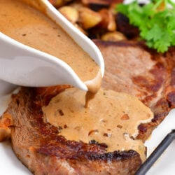 pepper sauce being poured over cooked steak on white platter