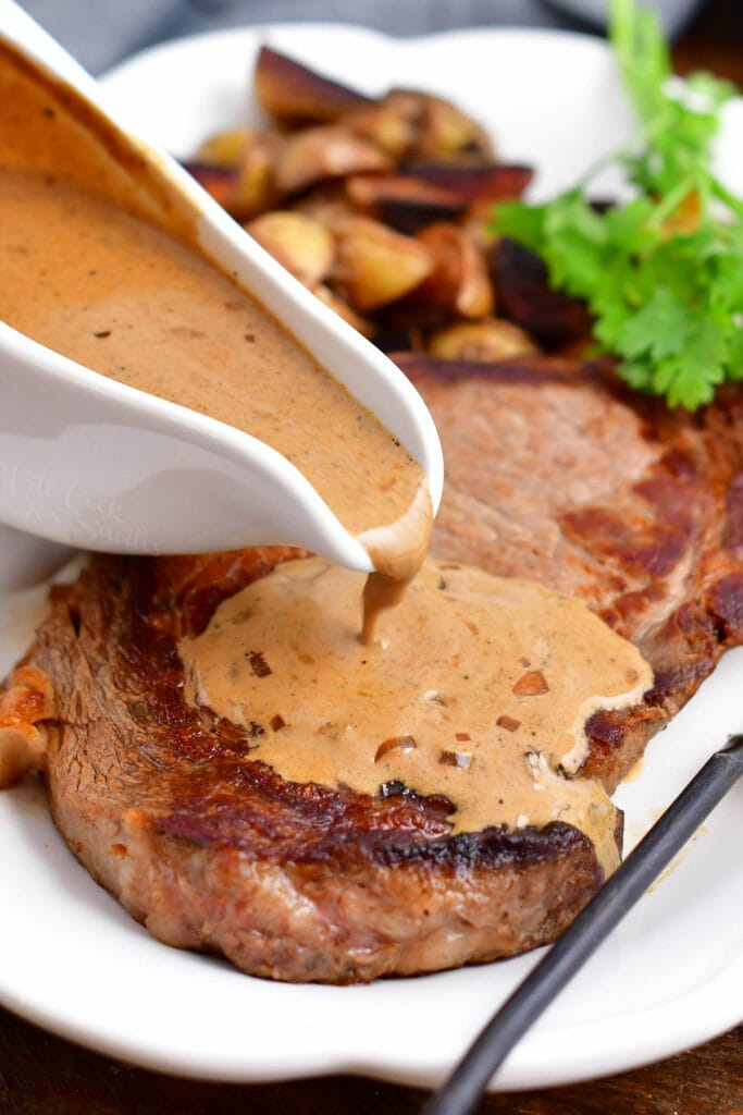 pepper sauce being poured over cooked steak