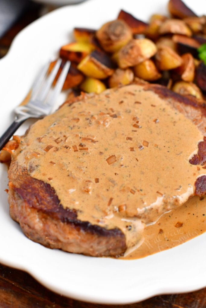 ribeye smothered in peppercorn sauce with roasted potatoes