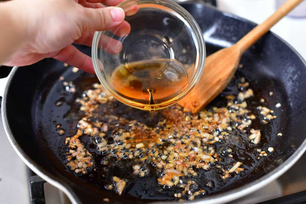 pouring cognac into a pan with shallots
