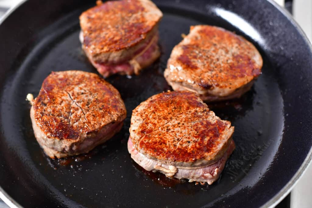 4 pan seared steaks in a skillet