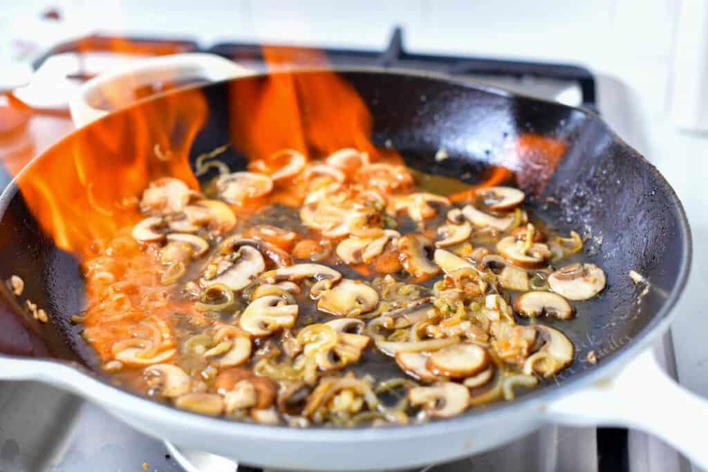 mushrooms flambe in hot skillet