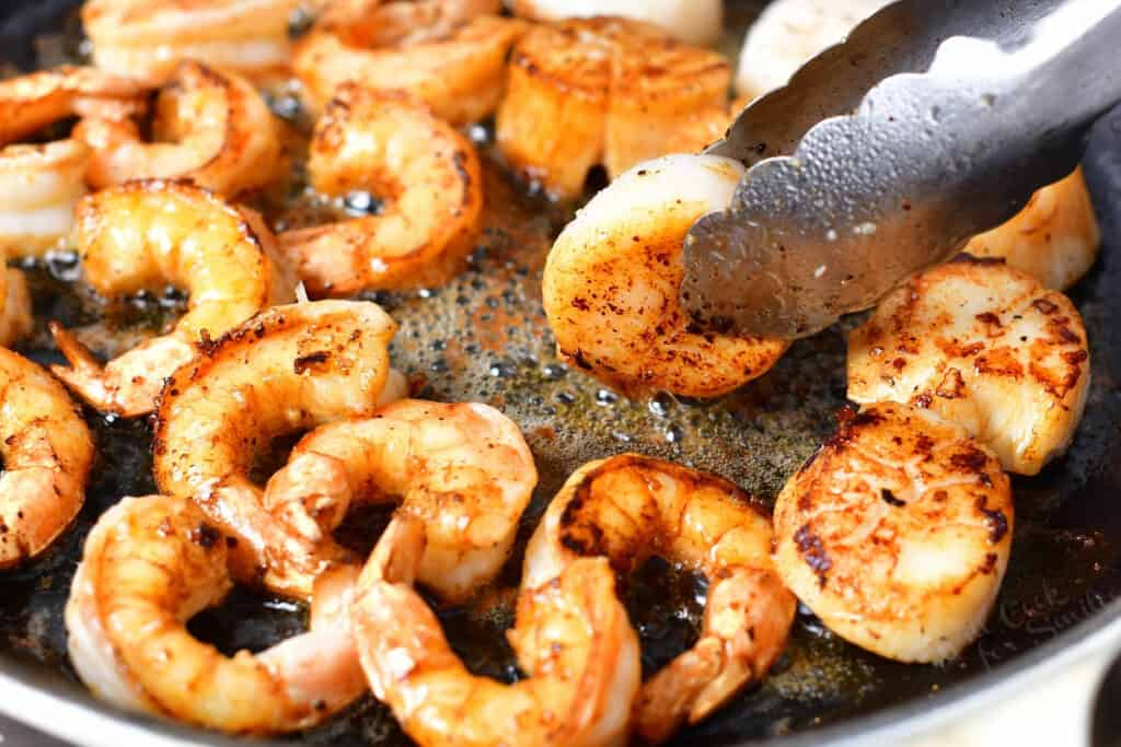 close up photo of shrimp and scallops being seared in a pan