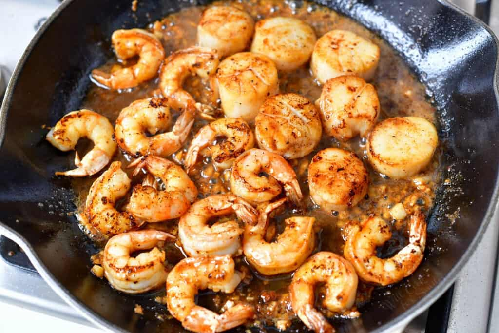 golden cooked scallops and shrimp in saute pan