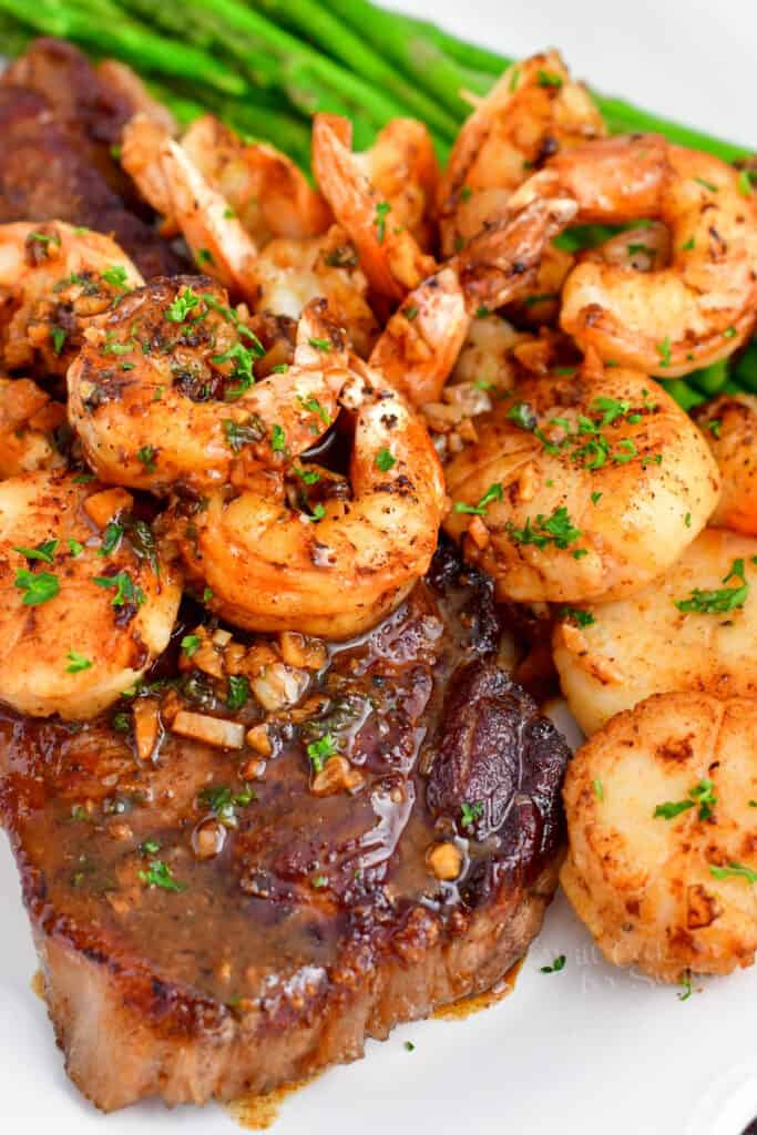 cooked steak and shrimp on plate with asparagus