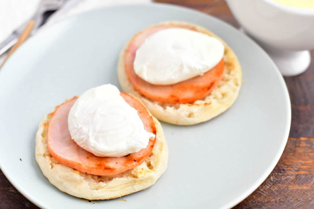 English muffins are on a plate and topped with Canadian bacon and poached eggs.
