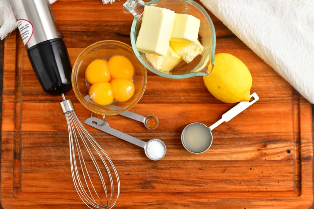 The ingredients for Eggs Benedict are placed on a wooden surface.