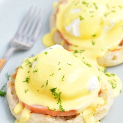 Two servings of Eggs Benedict are on a white plate.