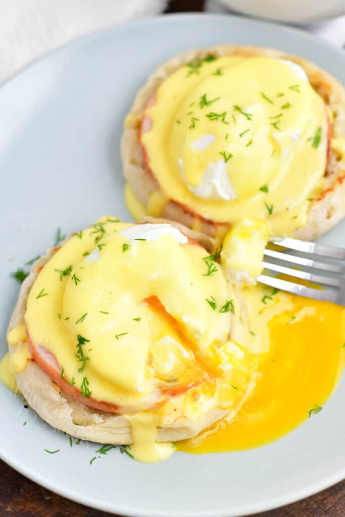 A fork has sliced into a serving of eggs Benedict, causing the yolk to run onto the white plate.