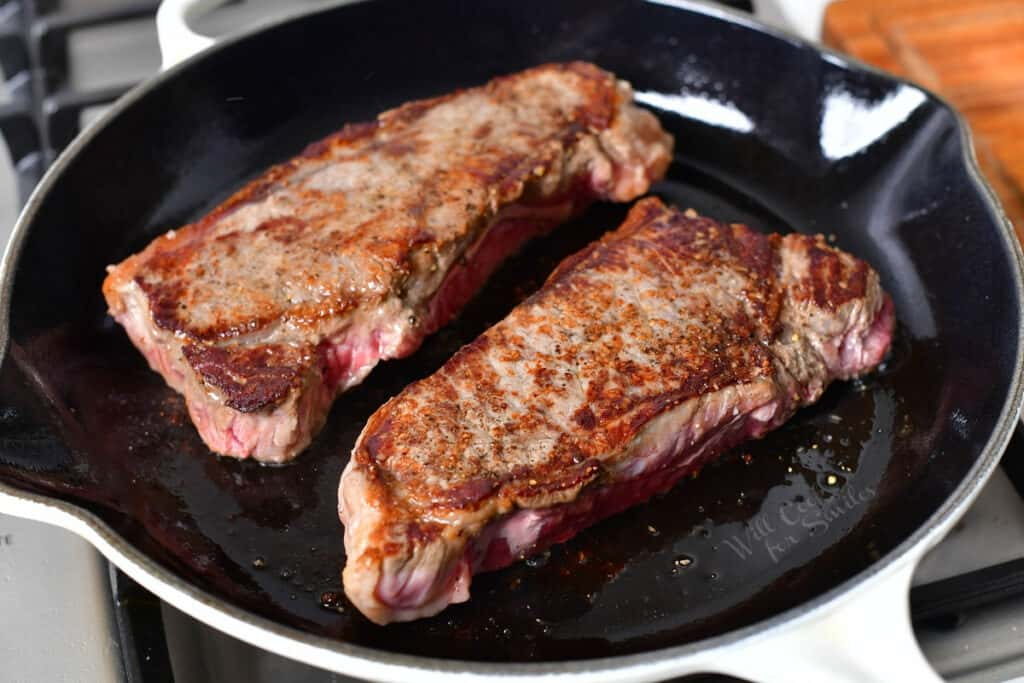 NY strip cooking in a cast iron skillet